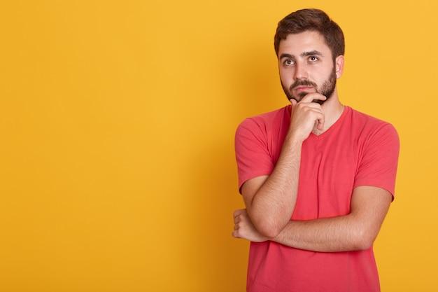 Sluit portret van sterke zekere kerel die zijn hand onder kin, studioschot houdt, laat me denken, draagt het mannetje rode toevallige t-shirt