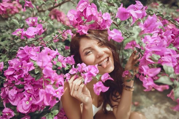 Sluit portretmeisje in het park op een achtergrond van roze bloemen