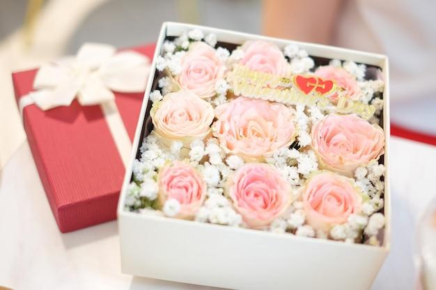 Sluit roze velen steeg in de rode giftdoos met lint voor bloemachtergrond of textuur - de dagconcept van de gelukkige valentijnskaart.