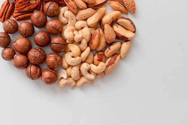 Sluit schot van geassorteerde bruine noten op een grijze achtergrond. macadami, cashewnoten, gehakte amandelen, pecannoten gezond voedsel