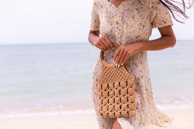 Sluit schot van vrouw in lichte zomer vliegende jurk gebreide tas houden op strand, zee op achtergrond.