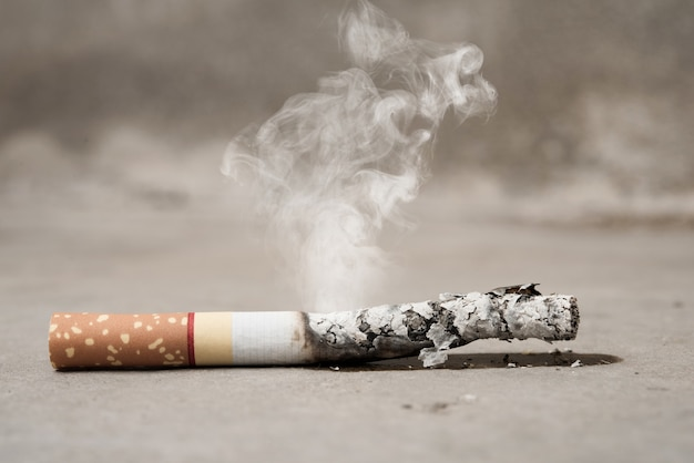 Sluit sigaret omhoog het branden op concrete vloer, einde met opheffend tabaksconcept
