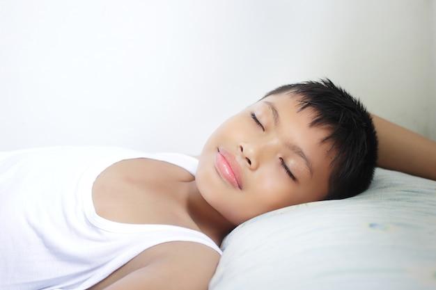 Sluit slaap van de gezichts aziatische jongen op zijn bed.