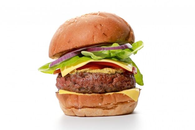 Sluit smakelijke eigengemaakte rundvleesburgers met kaas en sommige groenten, die op witte achtergrond omhoog wordt geïsoleerd
