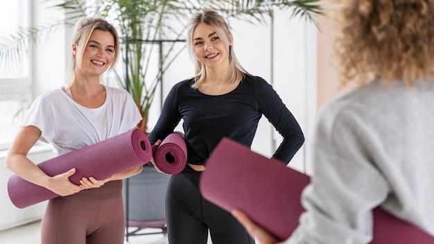 Sluit smileyvrouwen met yogamatten