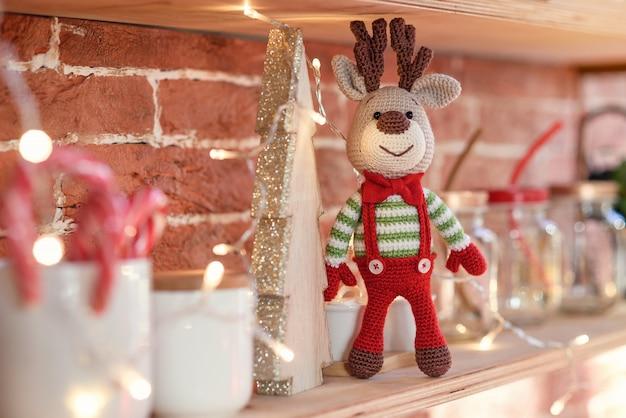 Sluit stuk speelgoed amigurumi-herten in gestreepte sweater en modieuze rode vlinderdastribunes op de houten plank dichtbij de verfraaide kerstmisboom en kerstmislichten.