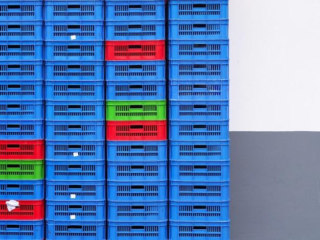 Sluit tot plastic de muurachtergrond van manden kleurrijke manden.