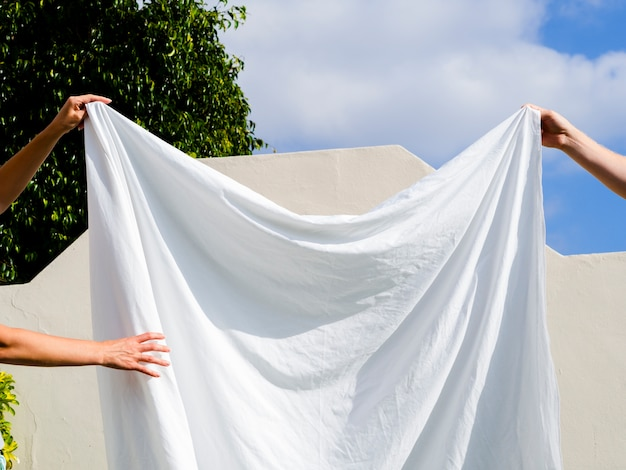 Sluit twee mensen omhoog hangend een wit blad op de lijn