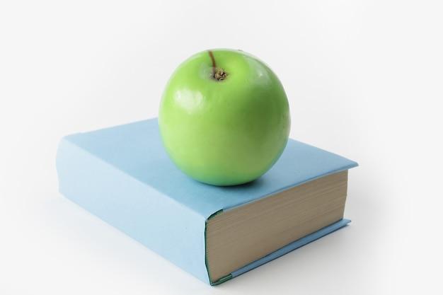 Sluit up.book en groene appel op witte achtergrond.