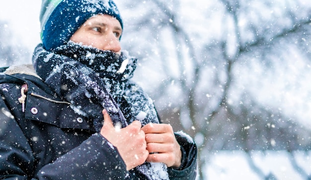 Sluit uprost man'sace met sjaal die door sneeuw op een de winterdag wordt behandeld