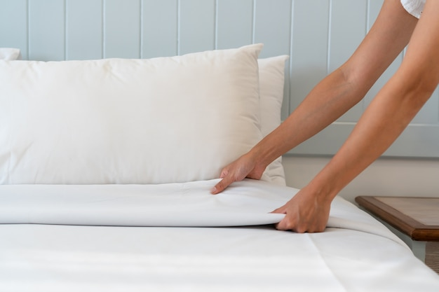 Sluit van de de opstellings wit bed van de vrouwenhand omhoog in hotelruimte, exemplaarruimte voor tekst.