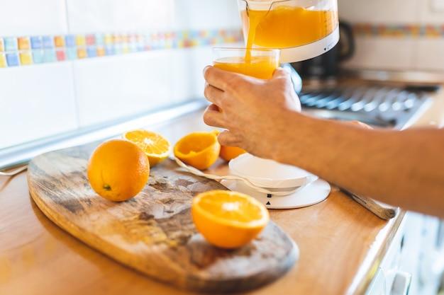 Sluit van de mens die jus d'orange maken gebruikend elektrische pers.