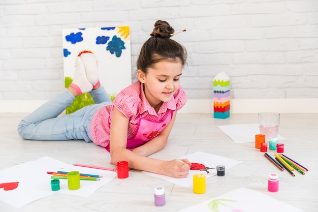 Sluit van een meisje die op vloer liggen die het lieveheersbeestje op witboek schilderen