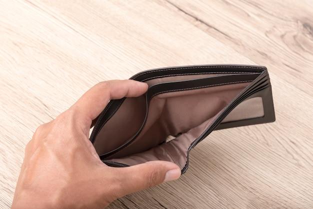 Sluit van hand opent omhoog een lege portefeuille op houten achtergrond.