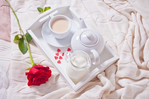 Sluit van kop thee met rood steeg op het witte dienblad