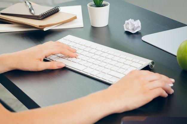 Sluit van omhoog vrouwelijke handen van vrouwenbeambte het typen op het toetsenbord