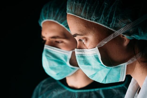 Sluit van twee zij vrouwelijke en mannelijke artsen die dragend medisch chirurgisch masker, medisch glb en virus beschermende kleding aan zwarte muur met exemplaarruimte werken. covid-19 de pandemie van het coronavirus.