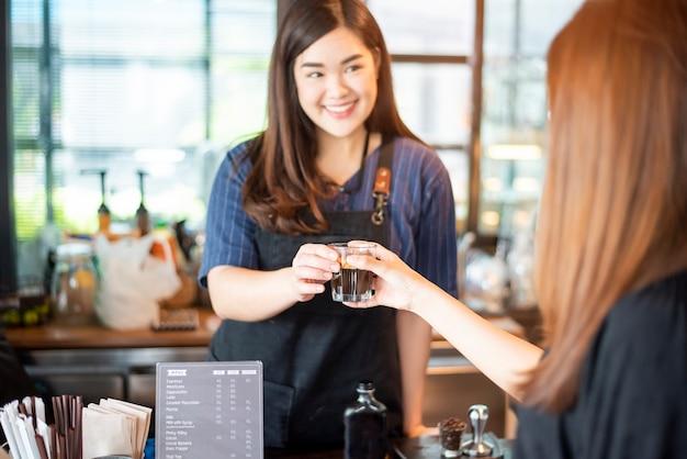 Sluit van vrouwelijke hand neemt omhoog hete koffie van barista