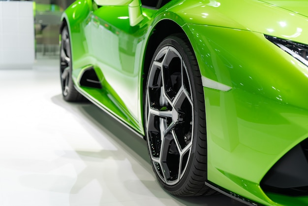 Sluit vooraan van nieuwe groene auto met het wielparkeren van de magnesiumlegering op autotoonzaal.