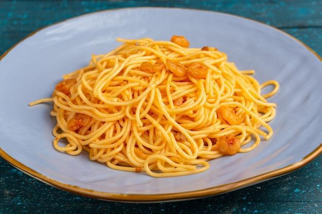 Sluit vooraanzicht gekookte italiaanse pasta lekker in blauw bord op blauw hout