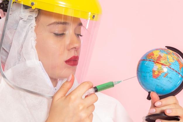 Sluit vooraanzicht jonge mooie vrouw in speciaal wit pak met beschermende helm injectie globe op roze