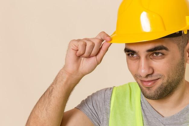 Sluit vooraanzicht mannelijke bouwer in gele helm poseren op lichte achtergrond