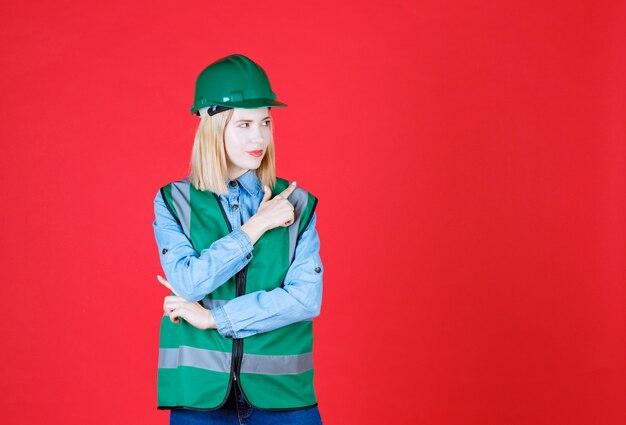 Sluit vooraanzicht van denkende vrouwelijke bouwer in uniform met groene hoed en omhoog op een rode muur