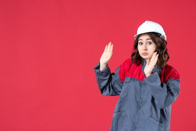 Sluit vooraanzicht van geschokte vrouwelijke bouwer in uniform met bouwvakker op geïsoleerde rode muur