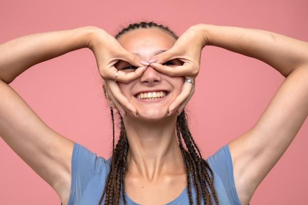 Sluit vooraanzicht van jong meisje dat enkel op roze glimlacht