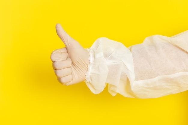 Sluit vooraanzicht van mannelijke wetenschappelijke werker in speciaal beschermend pak en als teken op gele muur tonen