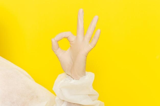 Sluit vooraanzicht van mannelijke wetenschappelijke werker in speciaal beschermend pak en goed teken op gele muur tonen