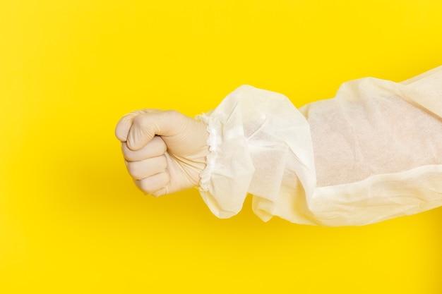 Sluit vooraanzicht van mannelijke wetenschappelijke werker in speciaal beschermend pak op gele muur