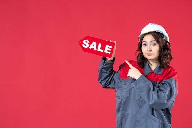 Sluit vooraanzicht van vrouwelijke werknemer in uniform die bouwvakker draagt en verkooppictogram op geïsoleerde rode muur richt
