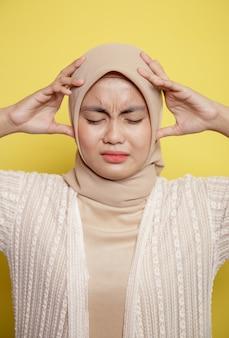 Sluit vrouw hijab met een duizelige uitdrukking omhoog denkend iets dat het hoofd houdt dat op gele achtergrond wordt geïsoleerd