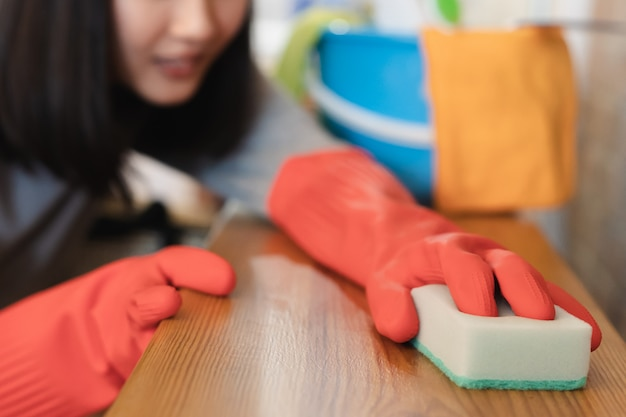 Sluit vrouw omhoog schoonmakende keuken gebruikend reinigingsmachine nevel en doek.