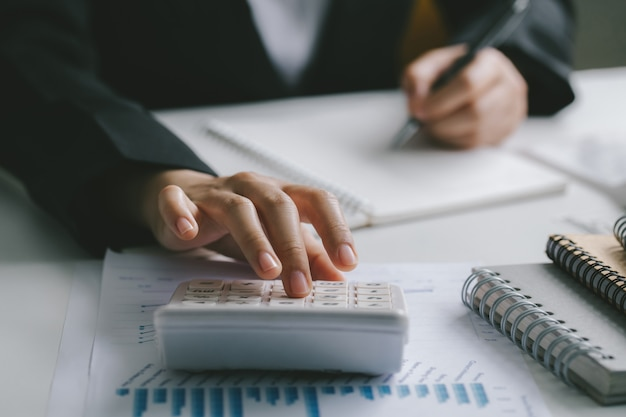 Sluit vrouwenhand gebruikend calculator en het schrijven maken nota met berekenen over financiënboekhouding. het concept van de financiënboekhouding