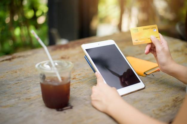 Sluit vrouwenhand houdt omhoog creditcard en gebruikt tablet in koffiewinkel