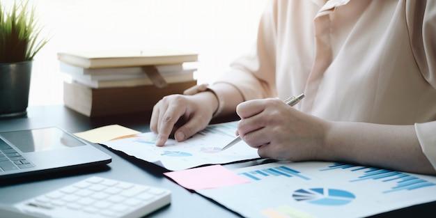Sluit zakenvrouw af die een grafiek controleert op een houten bureau op kantoor
