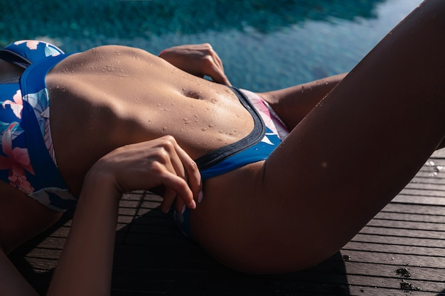 Sluiten: mooi model lichaam in blauwe bikini ontspant bij het zwembad. strandmode zomerkleding
