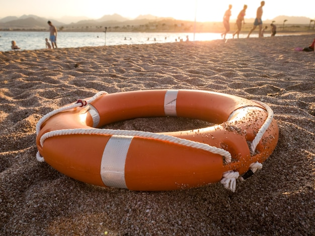 Sluitingsfoto van rode plastic levensreddende ring op zand van het zeestrand tegen prachtige zonsondergang boven de oceaan Premium Foto