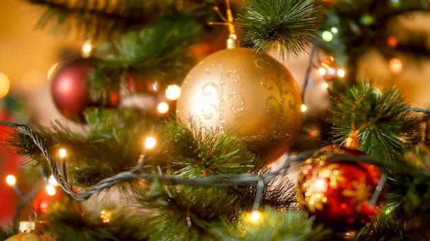 Sluitingsfoto van veel rode en gouden kerstballen die aan een versierde kerstboom in de woonkamer hangen