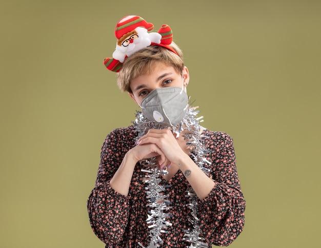 Sluw mooi meisje dragen santa claus hoofdband en klatergoud slinger rond nek met beschermend masker kijken camera handen bij elkaar houden geïsoleerd op olijfgroene achtergrond