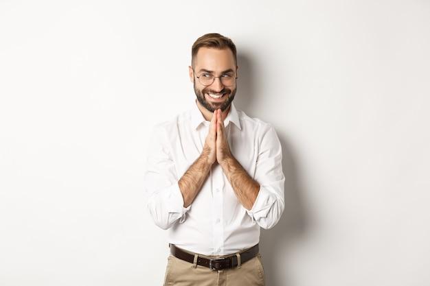 Sluwe en tevreden man die een idee heeft, handen wrijft en iets bedenkt met een blij gezicht, staande op een witte achtergrond.