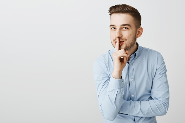 Sluwe grappige zakenman die met glimlach zwijgt, verrassing voorbereiden
