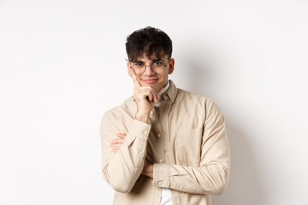 Sluwe jongeman die iets interessants ziet gebeuren, leunend gezicht op de arm en glimlachend sluw, geïntrigeerd, staande op een witte muur.