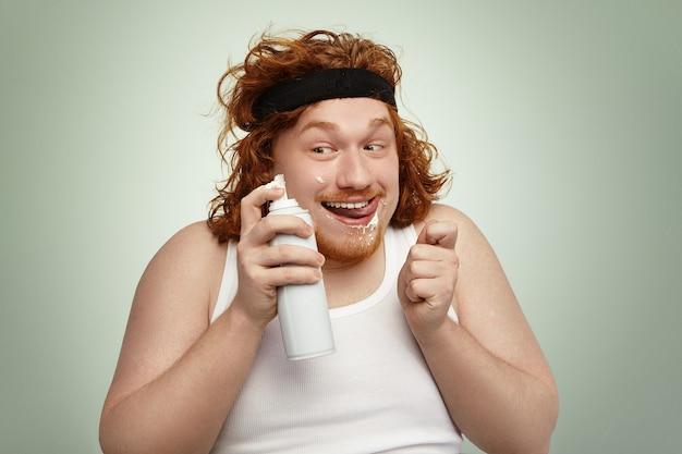 Sluwe roodharige dikke man in sportband en tanktop met spuitbus, met een gekke vrolijke blik