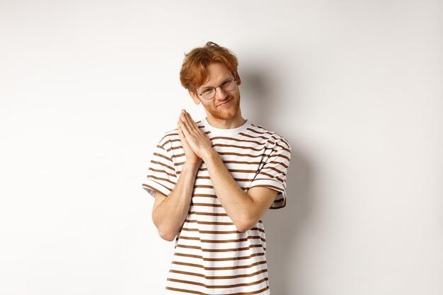 Sluwe roodharige man met een plan, handpalmen wrijvend en sluw kijkend naar de camera, grijns en scheel sluw, staande op een witte achtergrond.