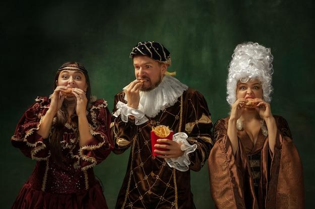 Smaak van toekomst. portret van middeleeuwse jongeren in vintage kleding op donkere achtergrond. modellen als een hertog en hertogin, prinses, koninklijke personen. concept vergelijking van moderne tijdperken, mode.