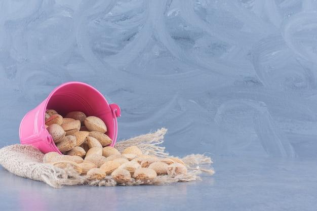 Smaakvolle amandelen morsen uit een kom, op de marmeren achtergrond.