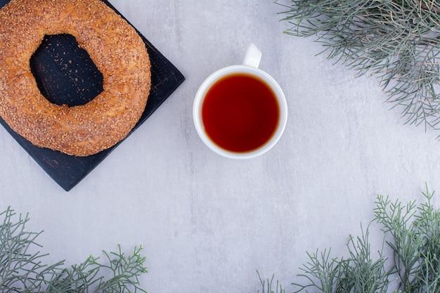 Smaakvolle bagel en een kopje thee op witte achtergrond.